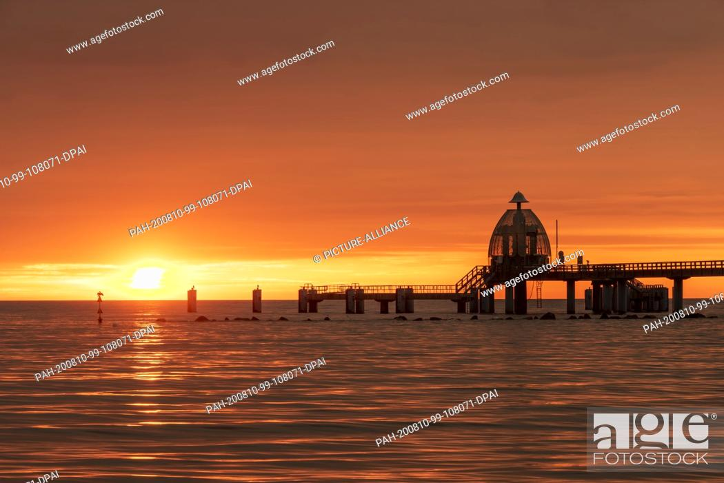 Stock Photo: 02 August 2020, Mecklenburg-Western Pomerania, Sellin: Sunrise at the pier with the famous diving gondola of the Baltic Sea resort on the island Rügel.