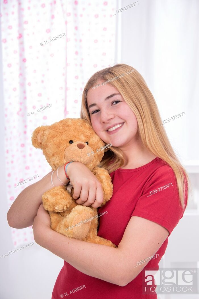 Stock Photo: young school girl, 15 year old, in red, with a broad smile, holding her teddy bear and cuddling it.