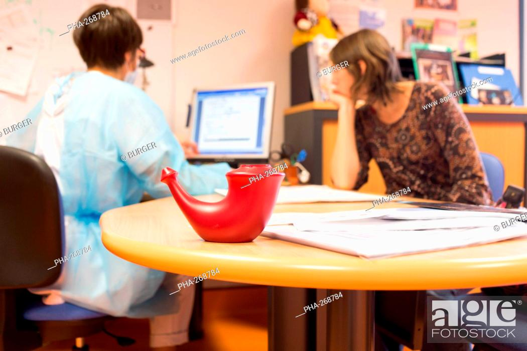 Stock Photo: Mother of a child with mucoviscidosis dialog with the physiotherapist. In the foreground, a lota, used for washing the nasal cavities.