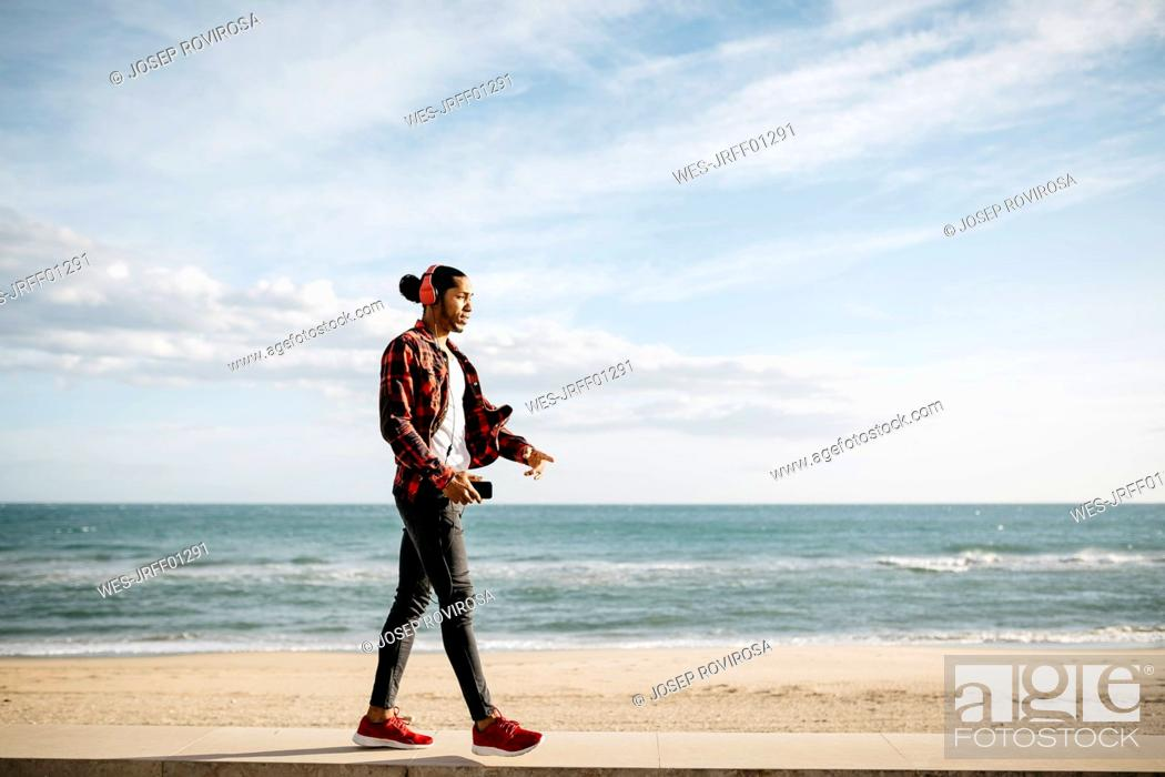 Photo de stock: Young man walking on wall in front of the beach promenade listening music with headphones.