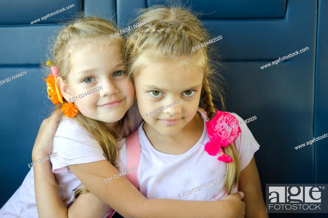 Stock Photo: Two girls hugging look in the frame, sitting in an electric train, close-up.