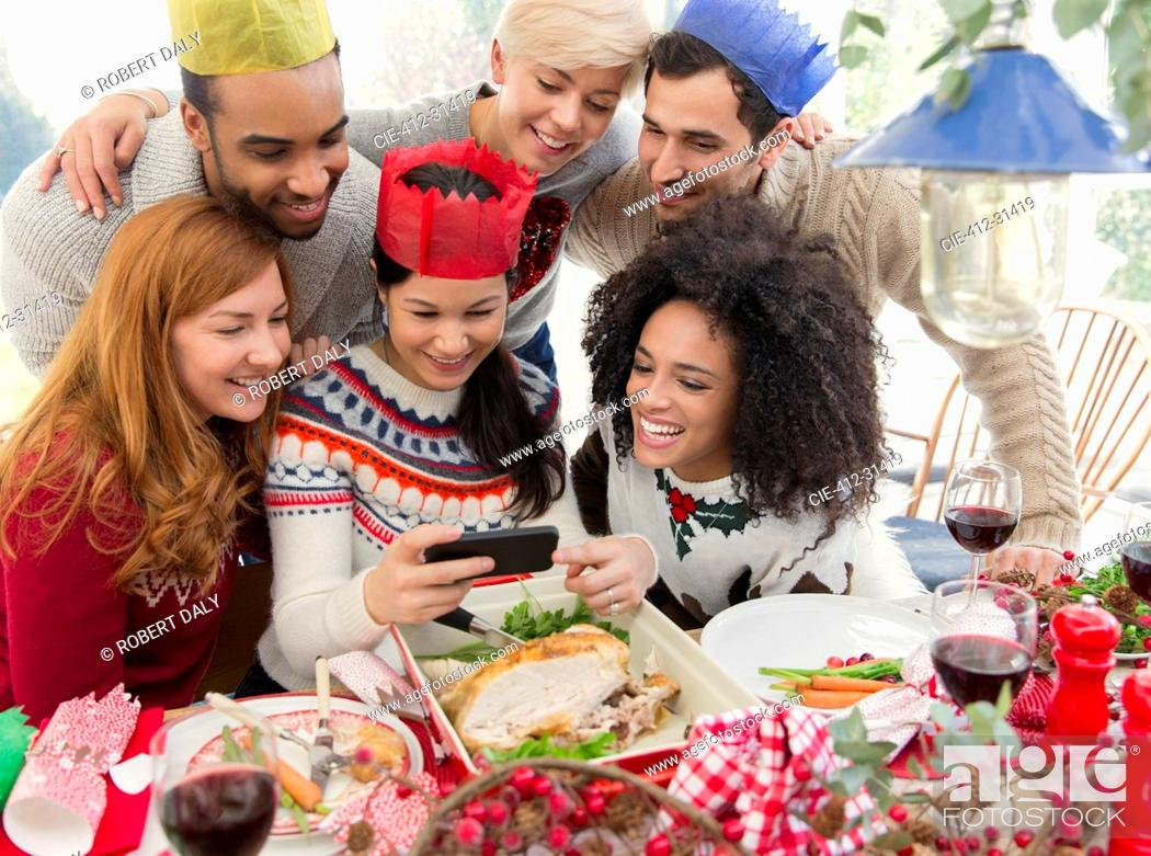 Stock Photo: Friends wearing paper crowns taking selfie at Christmas dinner.