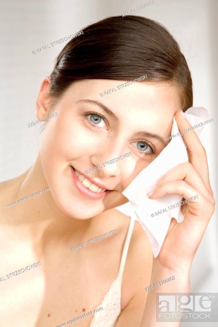 Stock Photo: young woman cleaning her face.