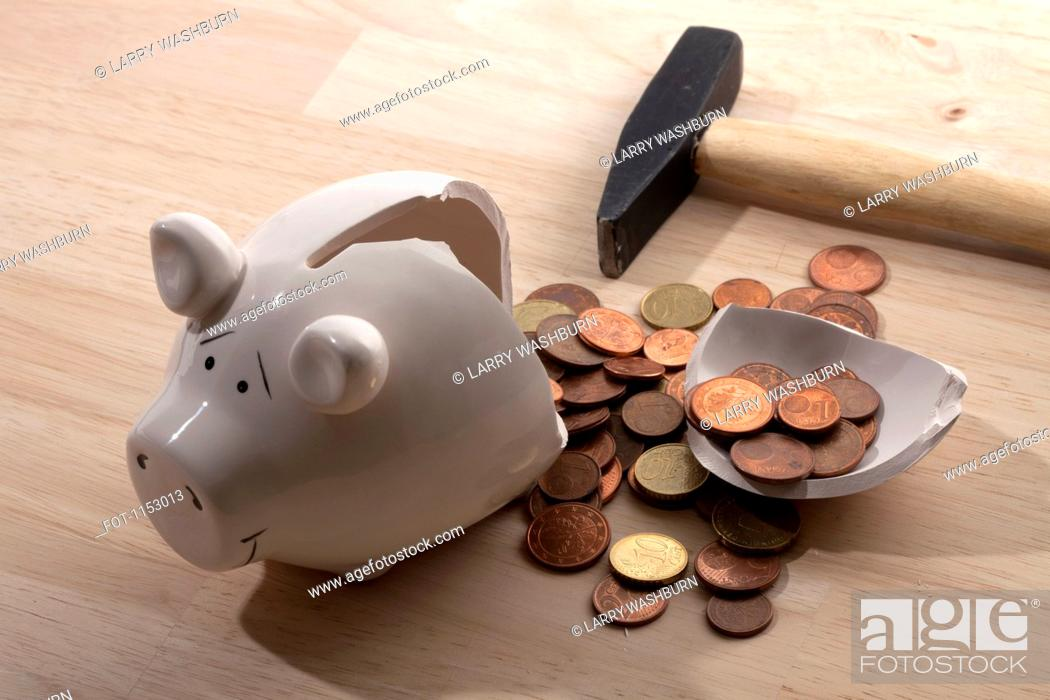Stock Photo: A hammer lying next to a broken piggy bank with Euro coins spilling out.