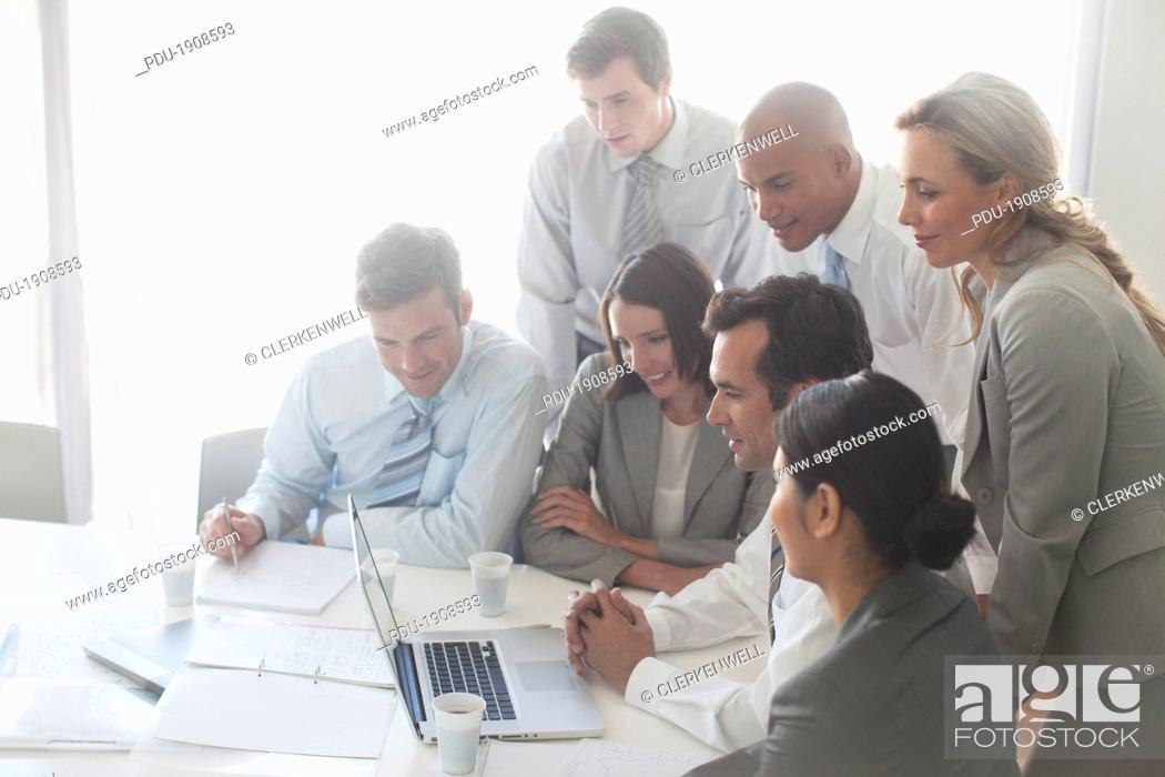 Stock Photo: Business people discussing while using laptop.