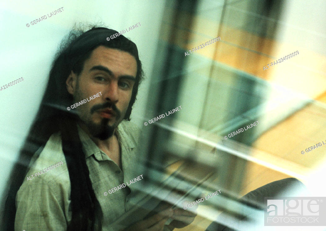Stock Photo: Man sitting looking at camera, view through glass.
