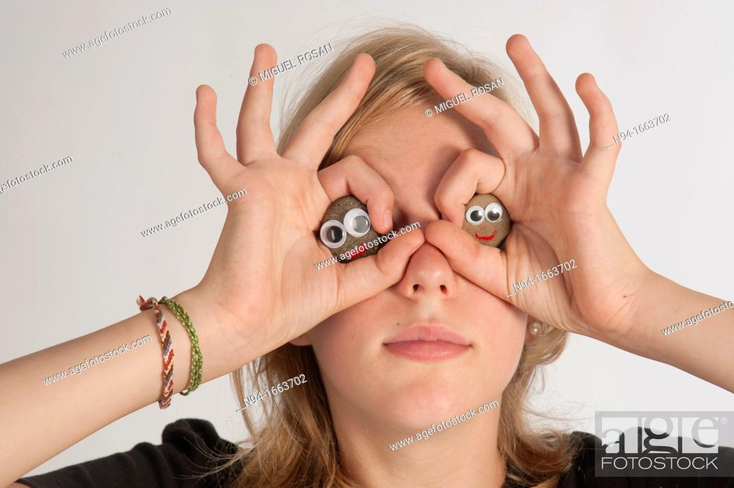 Stock Photo: Blonde girl holding her hands in the shape of a pair of binoculars in front of her eyes.