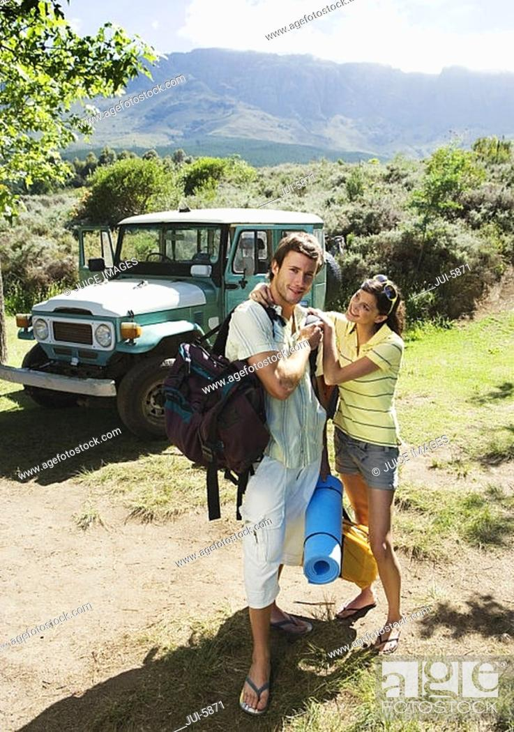 Stock Photo: Young couple unloading parked jeep at start of camping holiday, woman assisting man, smiling, portrait.