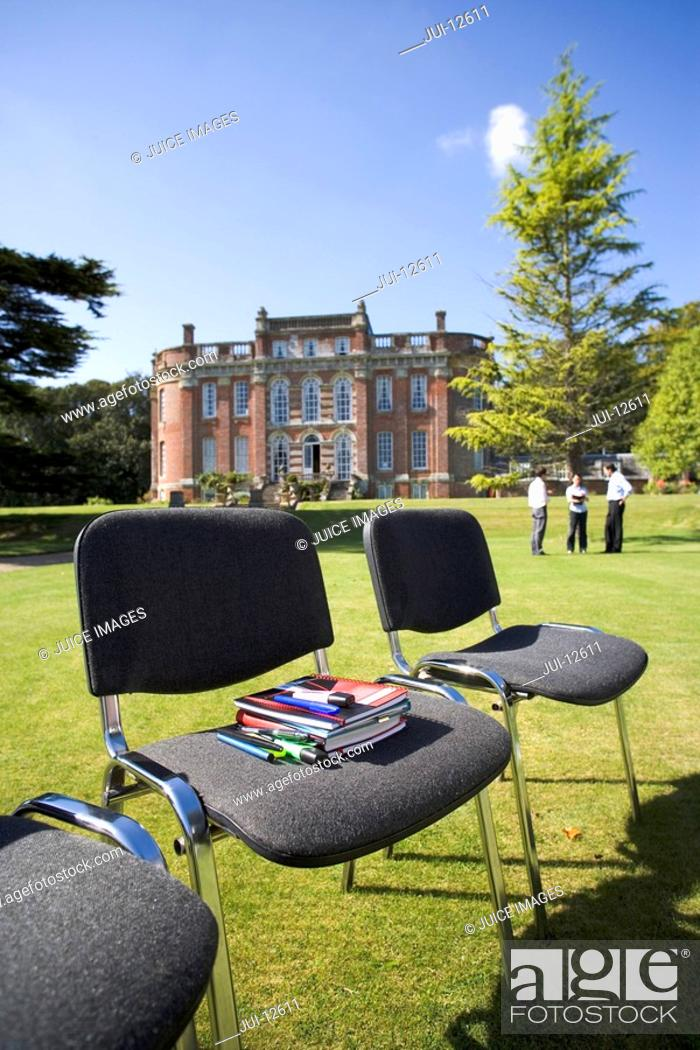 Stock Photo: Books and pens on chair on grass by manor house.