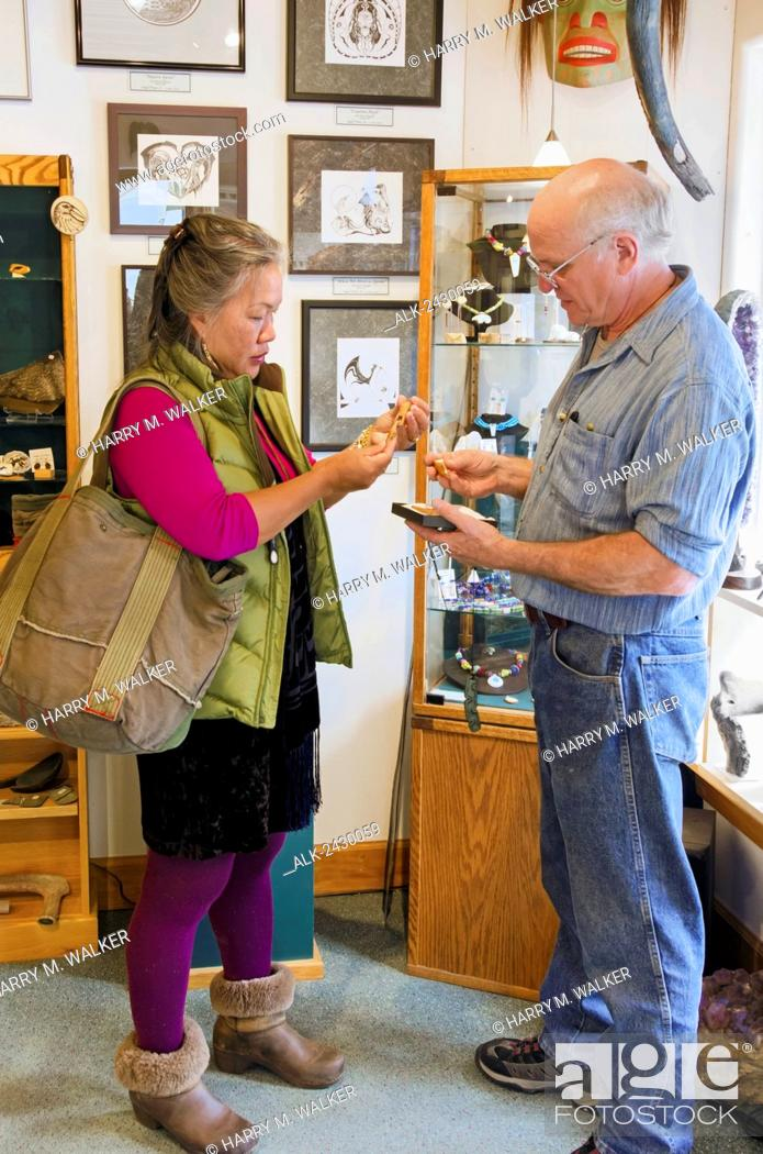 Stock Photo: Alaska artist Steve Stegall shows a tourist fossil walrus ivory in his gallery in the historic district of Skagway, Alaska.