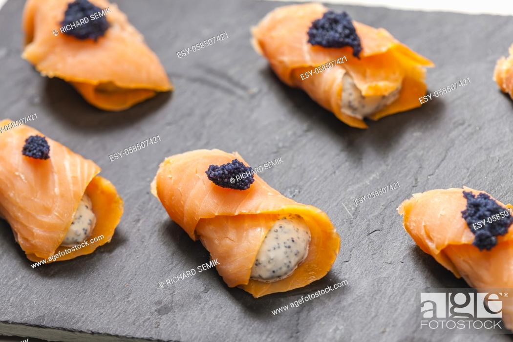 Stock Photo: smoked salmon rolls filled with cream cheese and black caviar.