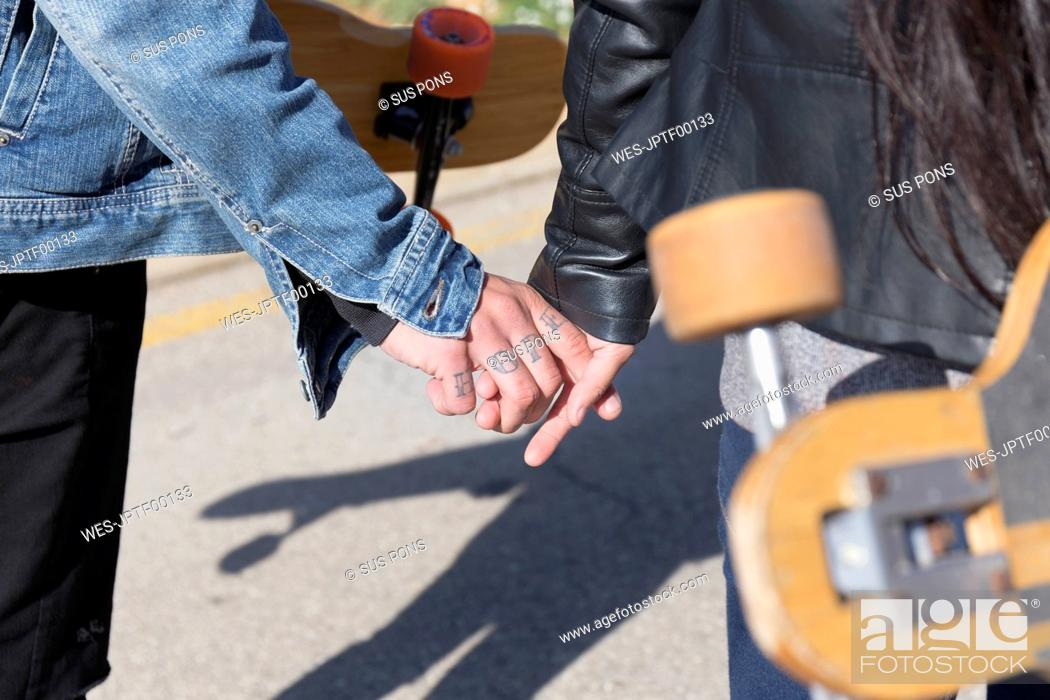 Stock Photo: Tattooed young man holding hand with his girlfriend, partial view.