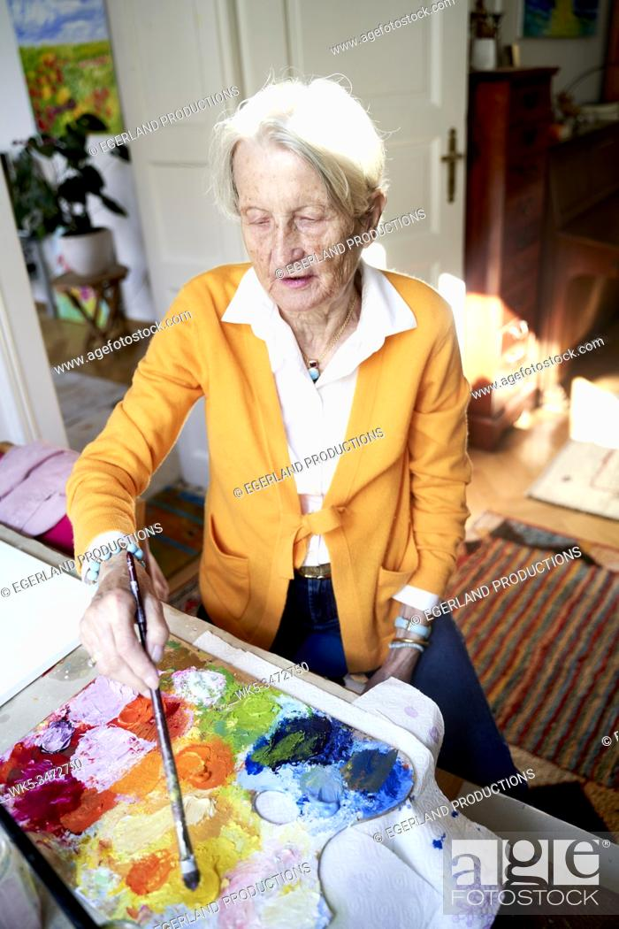 Stock Photo: Senior woman painting at home.