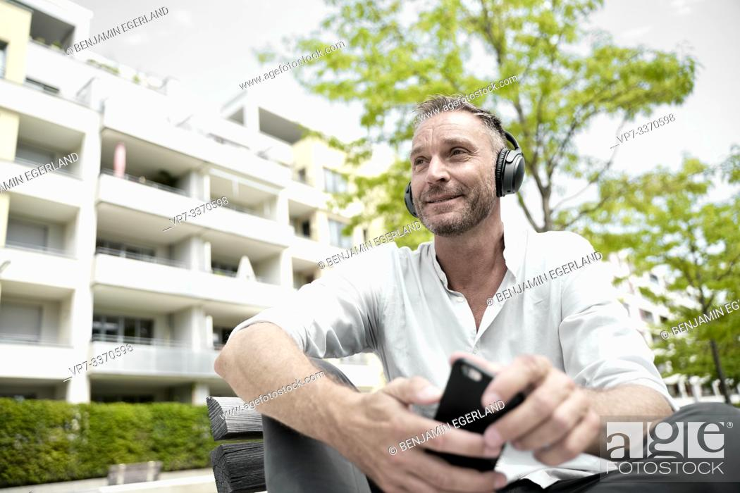 Photo de stock: confident best ager man with headphones and smartphone in residential area.