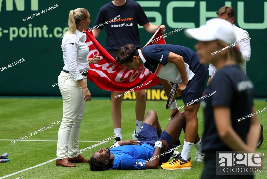 Stock Photo: 17 June 2019, North Rhine-Westphalia, Halle: Tennis: ATP-Tour singles, men, 1st round, Herbert (FRA) - Monfils (FRA). Gael Monfils (below) is injured on the.