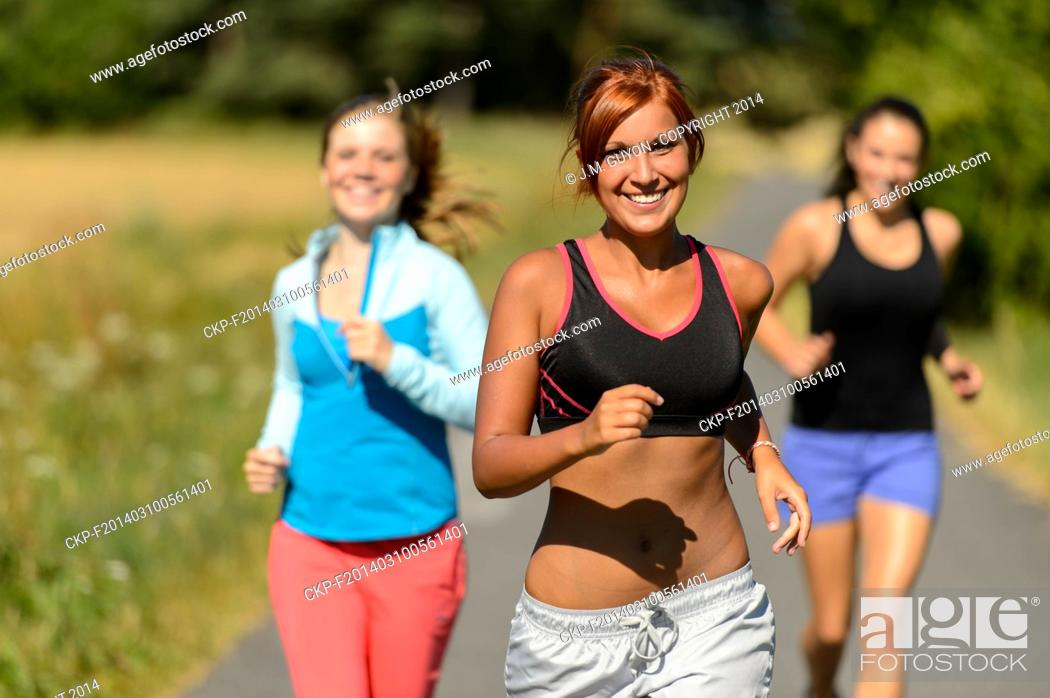 Imagen: Three friends running outdoors on sunny day smiling.