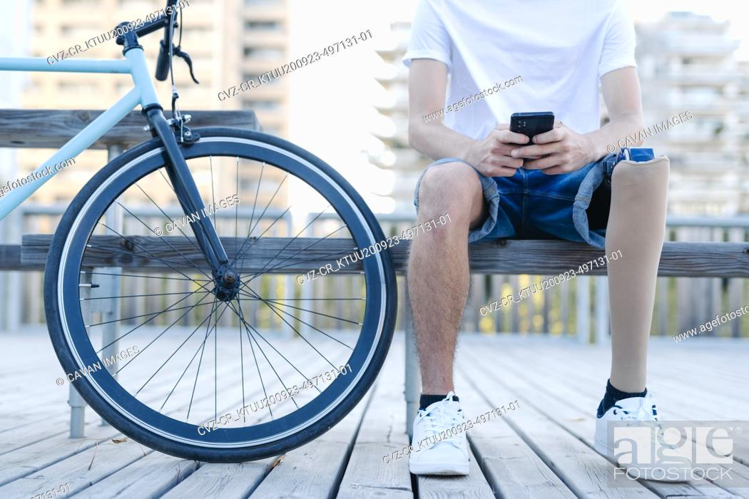 Photo de stock: Disabled bicyclist browsing smartphone in city.