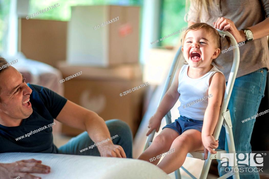 Stock Photo: Moving house: father and daughter laughing, daughter sitting on step stool.
