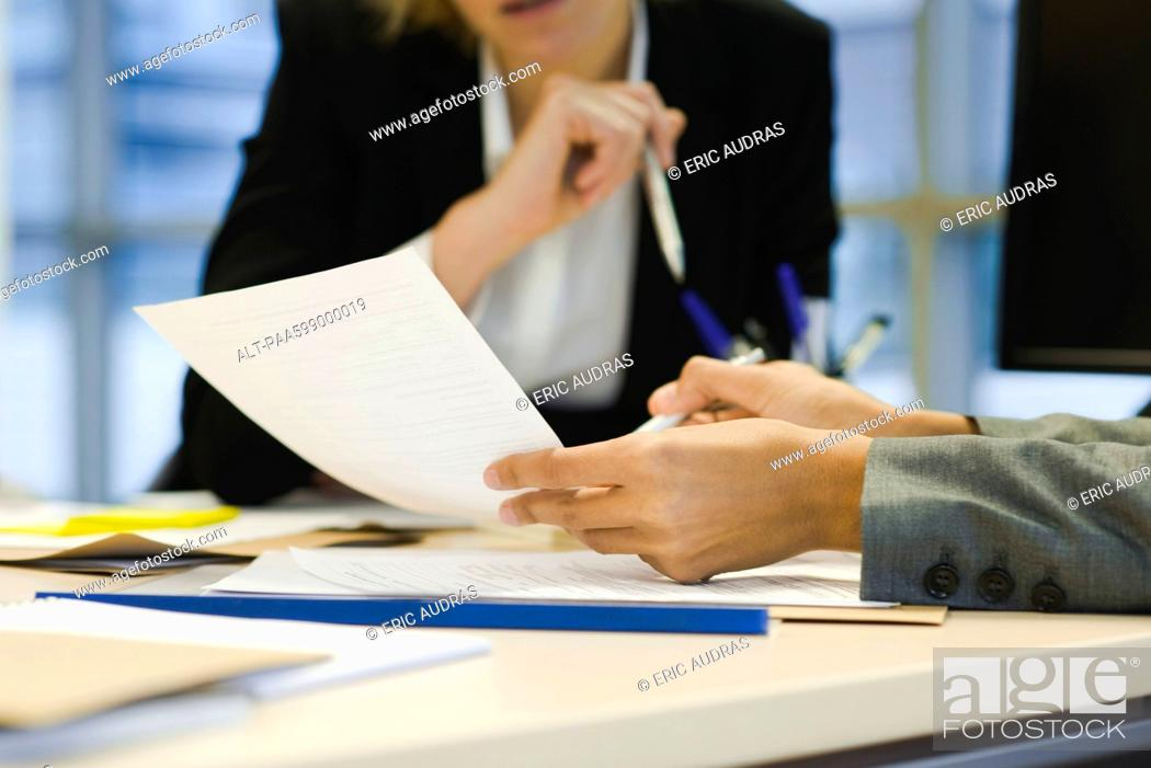Stock Photo: Executives discussing document, cropped.
