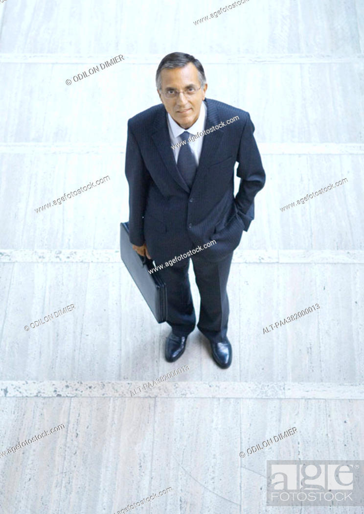 Stock Photo: Businessman standing with briefcase, high angle view.
