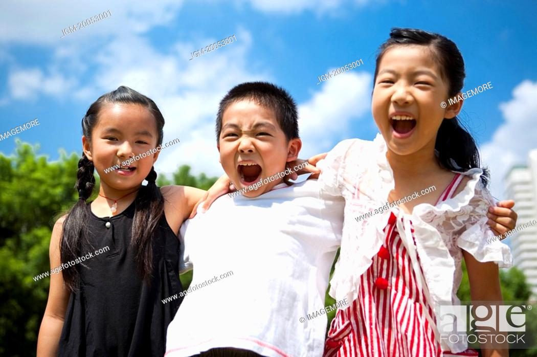 Stock Photo: Three children standing in a row with arms around and shouting happily.