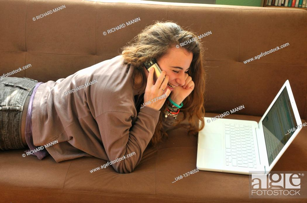 Stock Photo: Teen girl with laptop computer and cell phone.