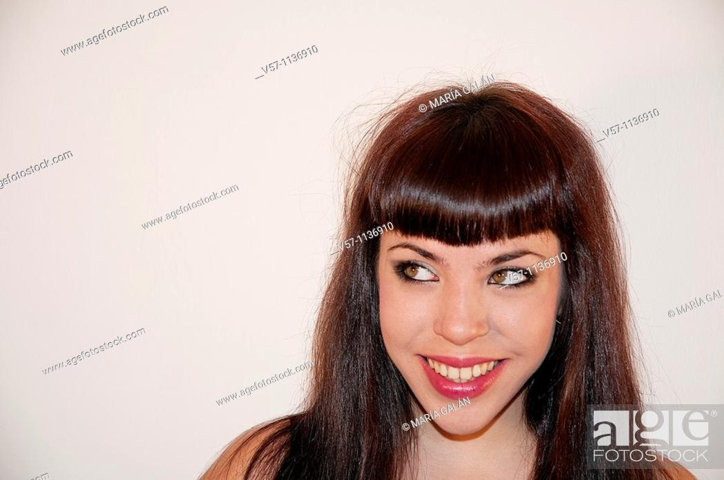 Stock Photo: Young woman smiling and looking up. Close view.