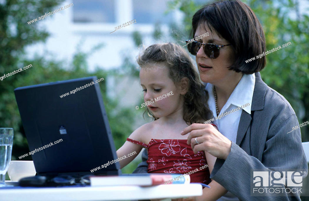 Stock Photo: A woman, businesswoman, mother, 40-45 45-50 years old, and a little girl, 1-5 5-10 years old, sitting at the table in the summerly garden, working at the laptop.