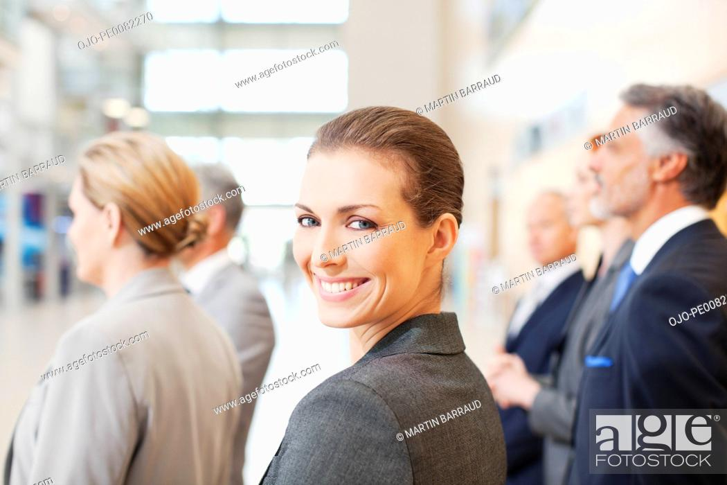 Stock Photo: Portrait of smiling businesswoman in lobby with co-workers.