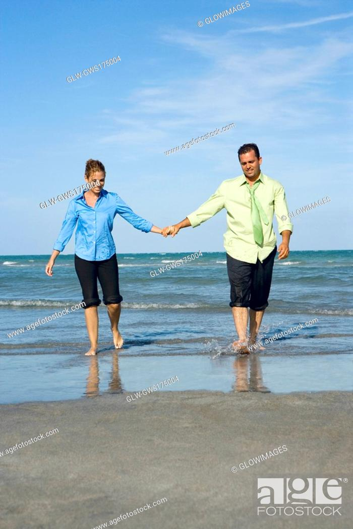 Stock Photo: Mid adult couple walking on the beach with holding each others hands.