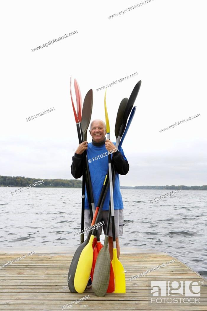 Stock Photo: Senior man holding oars on jetty.
