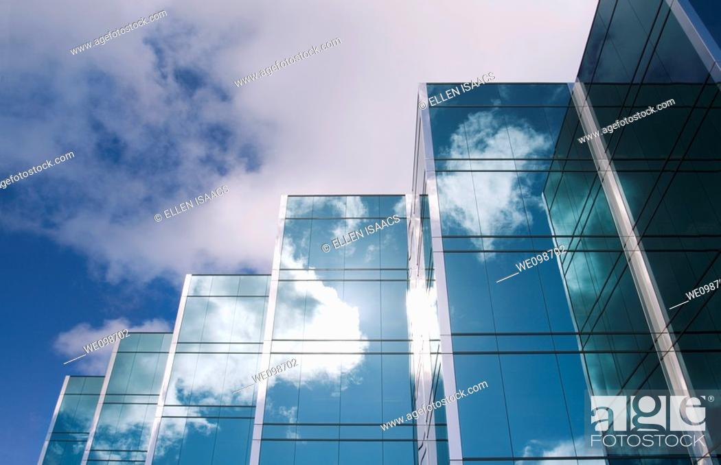 Stock Photo: Five towers of a sleek modern glass office building in Silicon Valley with the clouds and sky reflecting on the surface of the buildings.