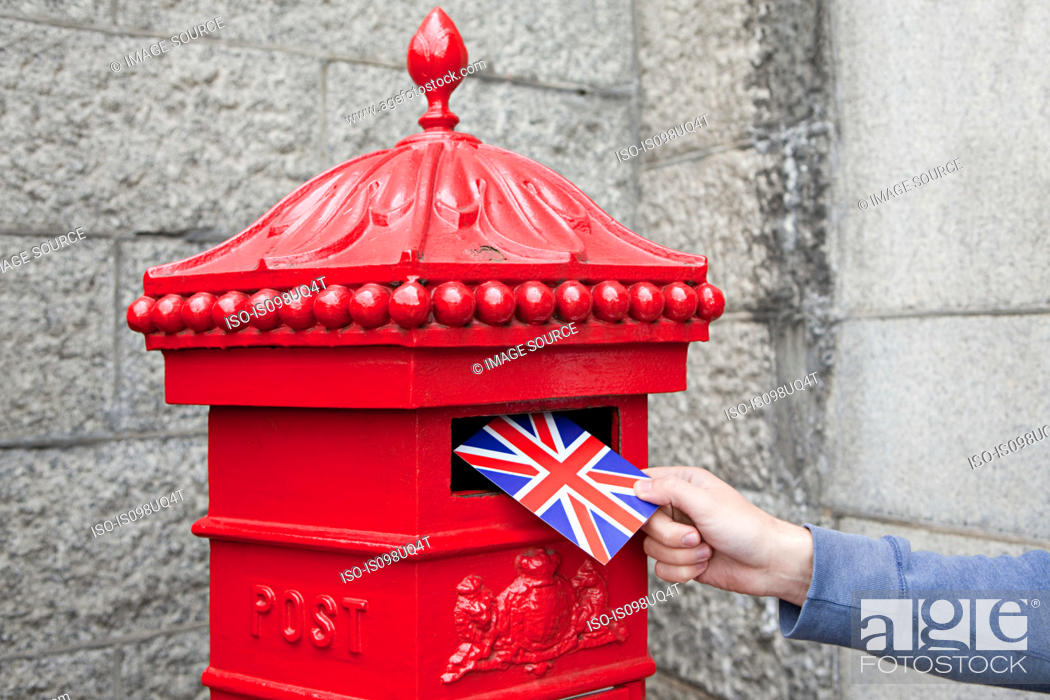 Stock Photo: Person putting postcard in post box, London.