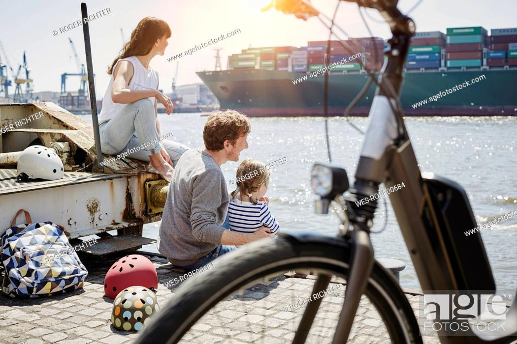 Stock Photo: Germany, Hamburg, family having a break from a bicycle tour at River Elbe watching a container ship.