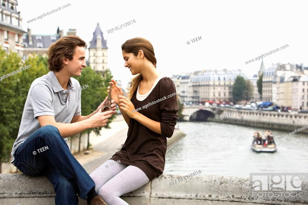Stock Photo: Young couple sitting on bridge, man giving present of miniature Eiffel Tower.