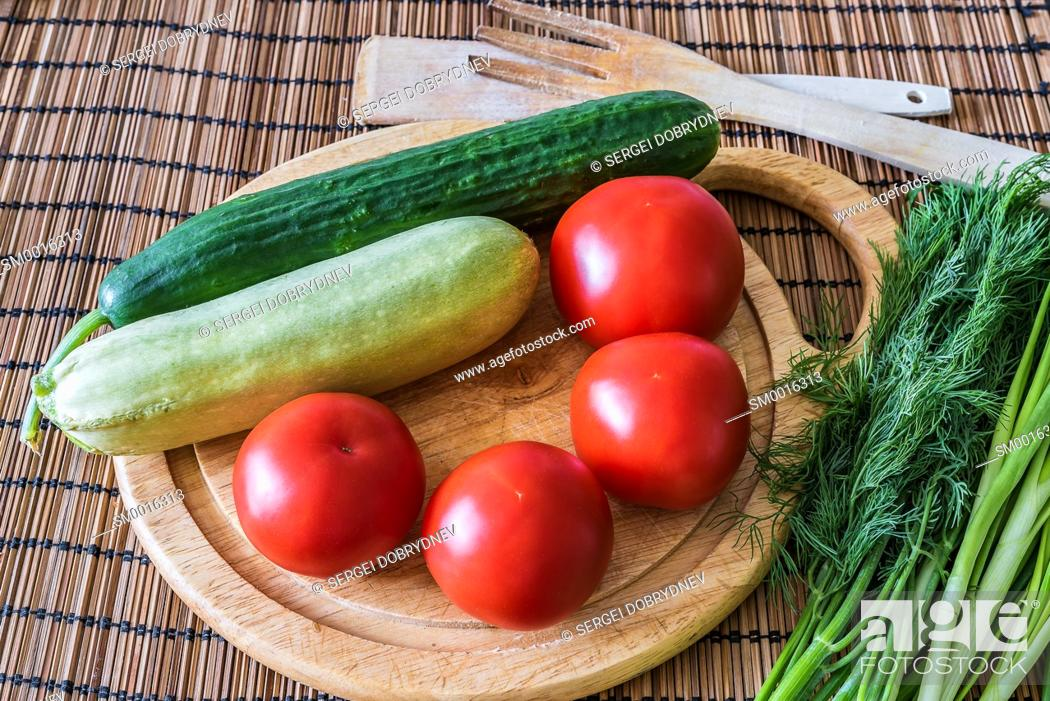 Stock Photo: Tomatoes, cucumber, zucchini, greens and a cutting board lie on the kitchen table.