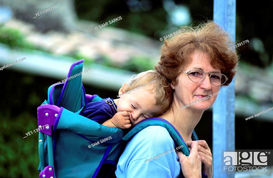 Photo de stock: Grandmother carrying her sleeping grandson in a backpack.