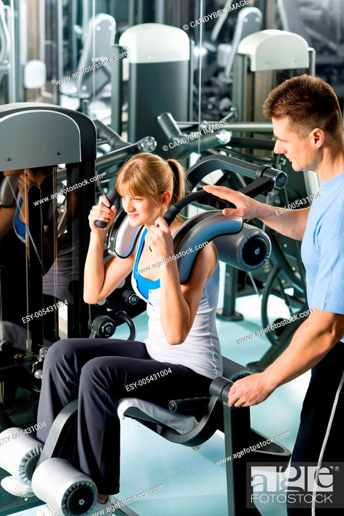 Stock Photo: Fitness center young woman exercise with trainer.