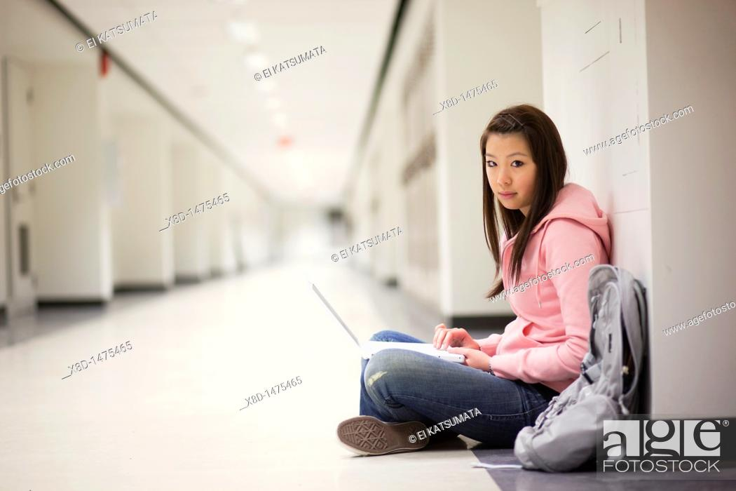 Stock Photo: Portrait of a young Asian woman using her laptop computer while sitting on floor in school hallway.