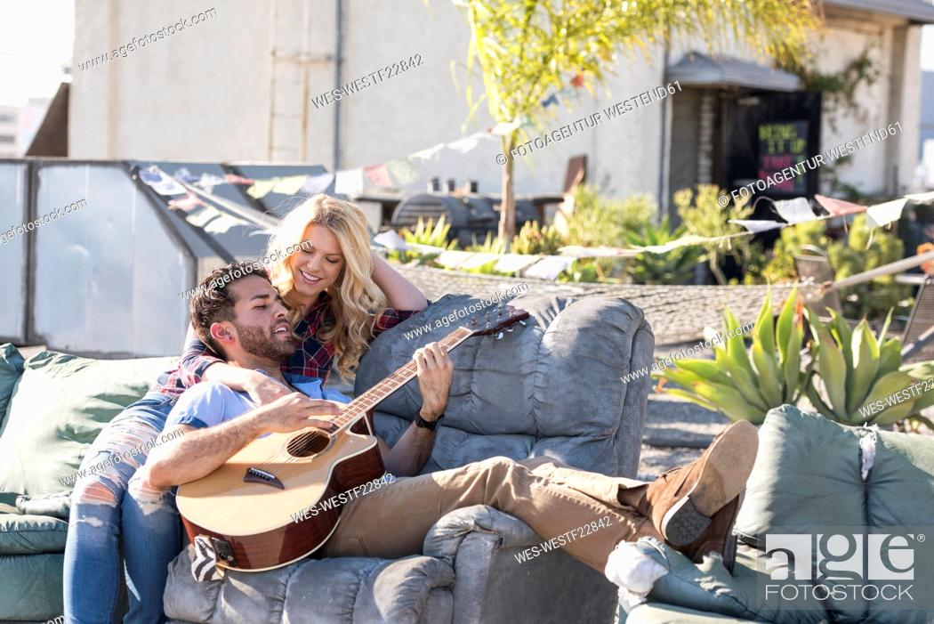 Imagen: Couple on rooptop sitting on sofa and playing guitar.