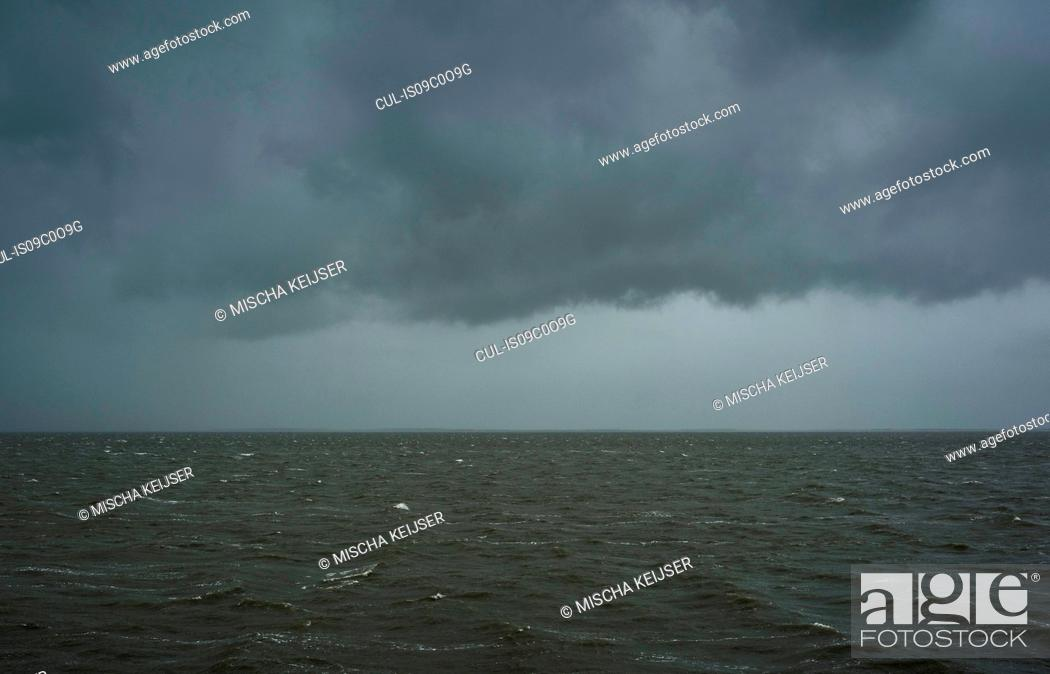 Stock Photo: Seascape with heavy rain and hail over the Waddensea in winter, Hollum, Friesland, Netherlands.