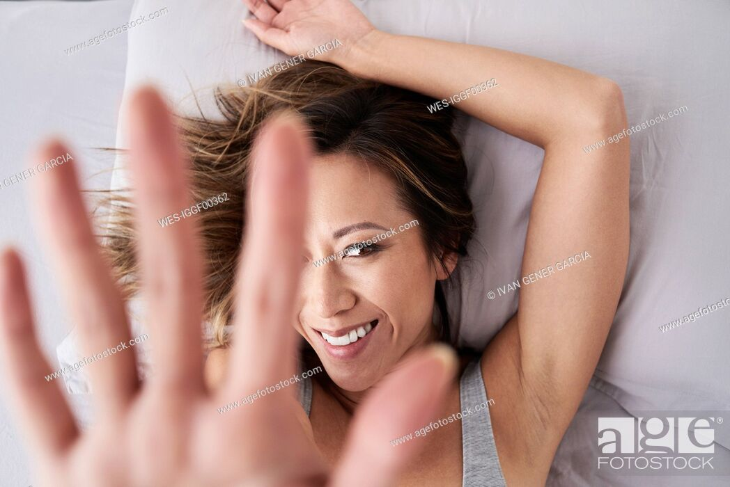 Stock Photo: Portrait of smiling woman lying in bed raising her hand.