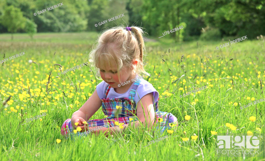 Stock Photo: Young girl sat in buttercup meadow.