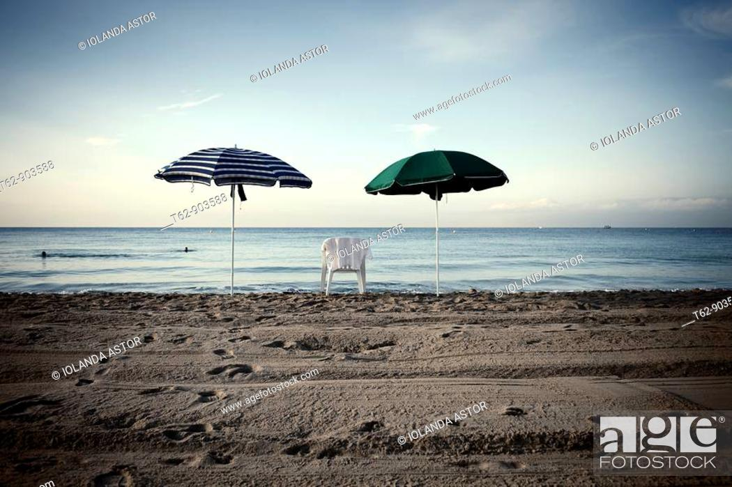 Stock Photo: A chair and two umbrellas on the beach  Mediterranean Sea coast  Black and White.