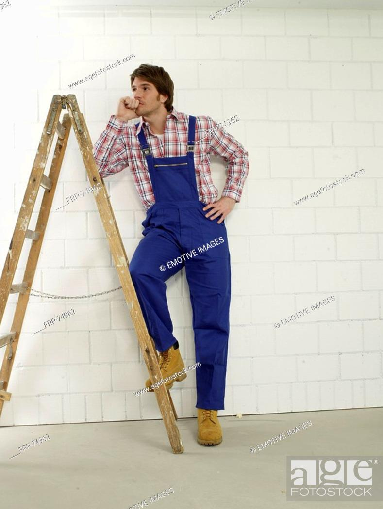 Stock Photo: Man wearing work wear is standing next to a ladder.