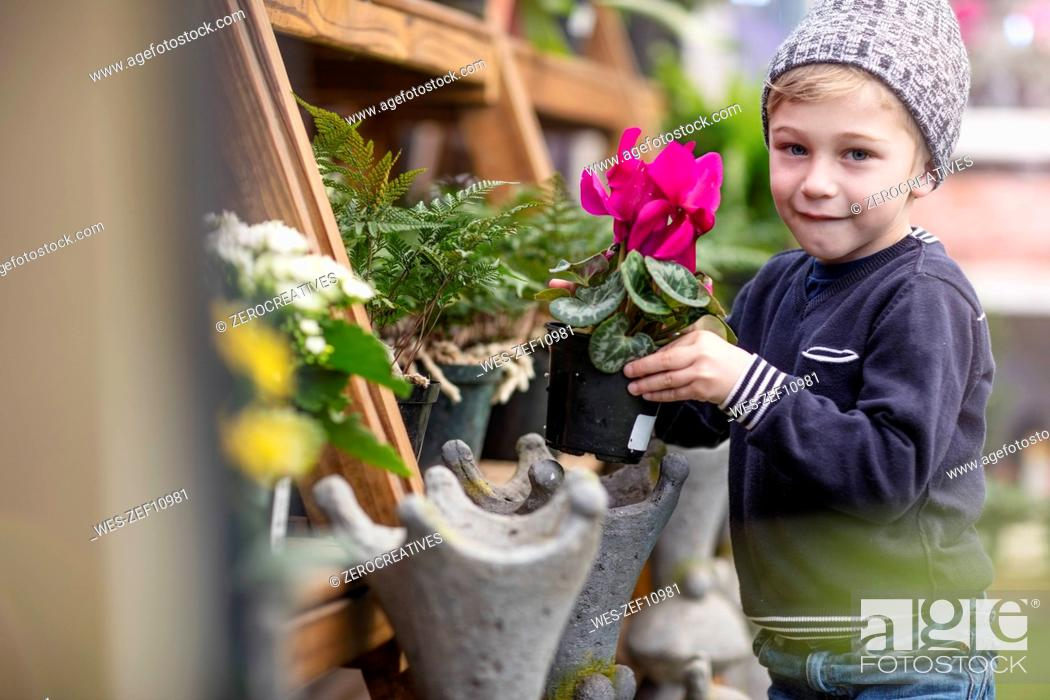 Stock Photo: Boy with flower pot at garden centre.