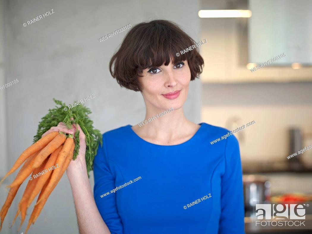 Stock Photo: Germany, Cologne, Young woman with carrots in kitchen, smiling, portrait.