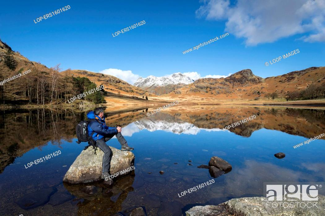 Stock Photo: Rambler at Blea Tarn and The Langdale Pikes in winter.