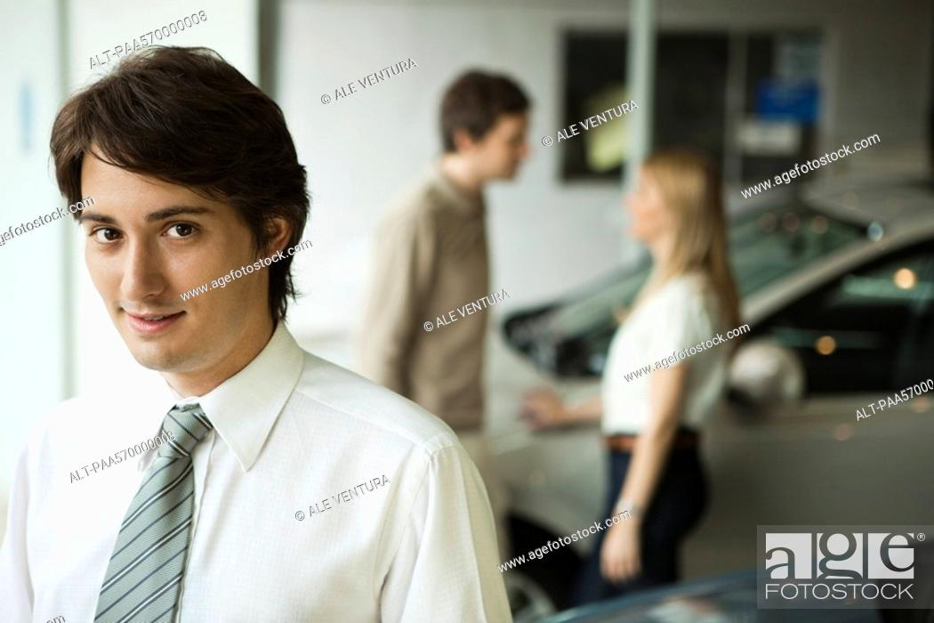 Stock Photo: Car salesman in dealership showroom, potential buyers in background.