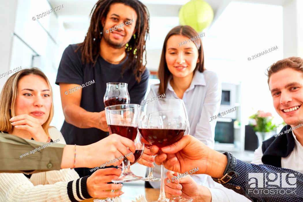 Imagen: Glückliche Gruppe Freunde stößt zusammen mit einem Glas Rotwein in der Küche an und feiert.